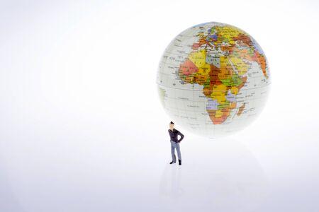 ittle: ittle model globe by the side of  man figure