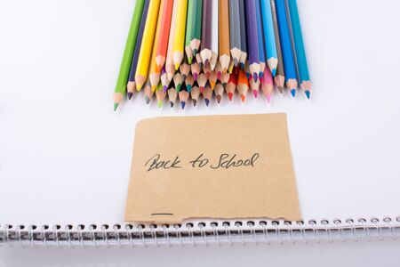 pedagogy: Color pencils and back to school title on a notebook Stock Photo