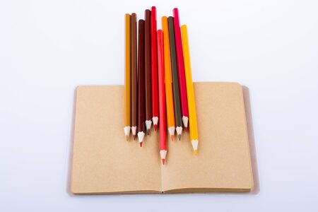 pedagogy: Color pencils placed on a brown notebook