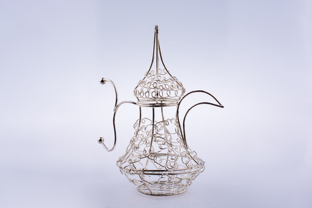 Silver color metal jug over a glass on a white background