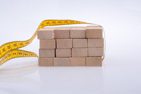 Yellow color measuring tape around domino pieces