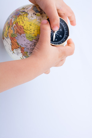 Hand holding a compass and a globe on white background