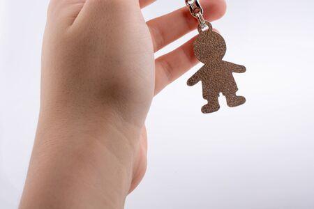 keyholder: Man shaped keyholder in hand on white background