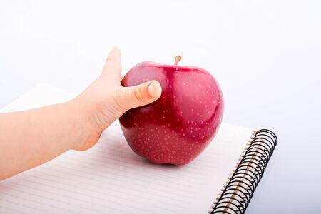 Hand holding a red apple on a notebook a white background Stock Photo