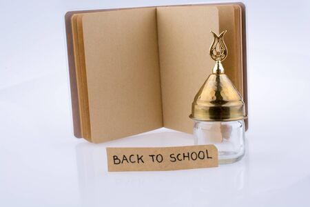 pedagogy: Color pencil, glass bottle and back to school title on a notebook Stock Photo
