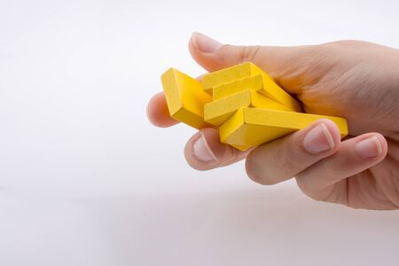 Hand holding yellow color domino pieces in hand