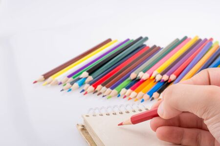 pedagogy: Hand holding a pencil beside the colorful pencils  on a white background