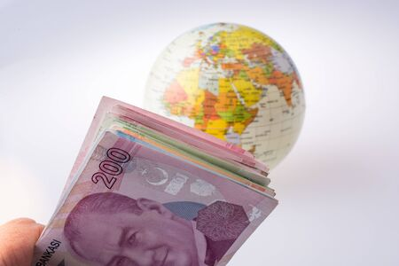Turkish Lira banknotes by the side of a model globe on white background