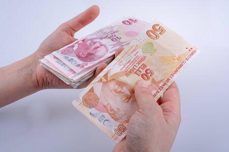 instability: Hand holding Turksh Lira banknotes  on white background Stock Photo