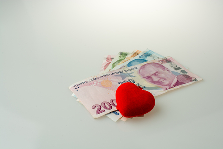 Turkish Lira banknotes by the side of a red color heart shaped object on white background Stock Photo