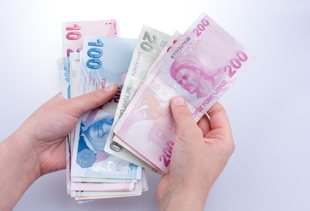 Hand holding Turksh Lira banknotes  on white background Standard-Bild