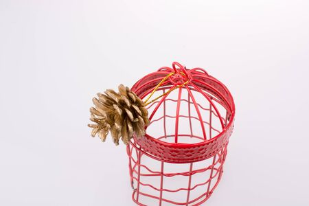 Pine cone in a red  bird cage on a white background