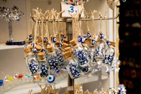 Little transparent glass bottle filled with blue evil eye beads
