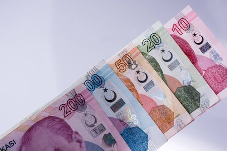 instability: Turksh Lira banknotes of various color, pattern and value on white background Stock Photo