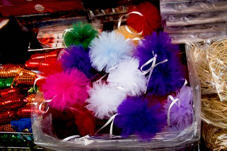 Set of different colours and shapes of pompoms in an open market Stock Photo