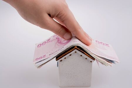 Hand holding Turkish Lira banknotes on the roof of a model house  on white background