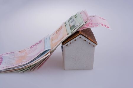 Turkish Lira banknotes on the roof of a model house  on white background