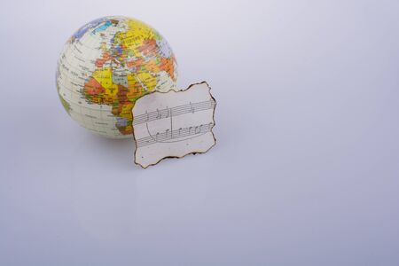 Musical notes on a burnt paper and a little model globe