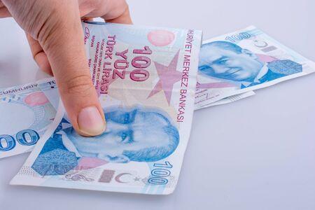 Hand holding 100 Turksh Lira banknotes  on white background