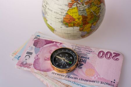 Turkish Lira banknotes by the side of a compass on white background Stock Photo