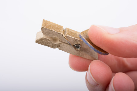 Hand holding a small wooden clothespin in hand