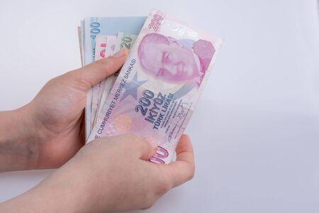 Hand holding Turksh Lira banknotes  on white background Stock Photo