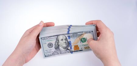 instability: Human hand holding American dollar bill as money isolated on white