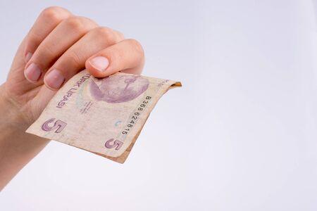 Hand holding 5 Turksh Lira banknote  on white background