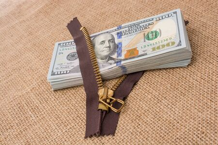 Banknote bundle of US dollar and a brown zipper