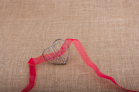 fiance: band and Heart shaped cage on linen canvas Stock Photo