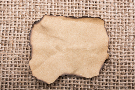 business backgound: Piece of  burnt paper placed on a linen canvas Stock Photo