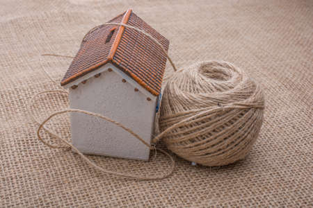 domicile: Thread wrapped around  a model house  on a brown background