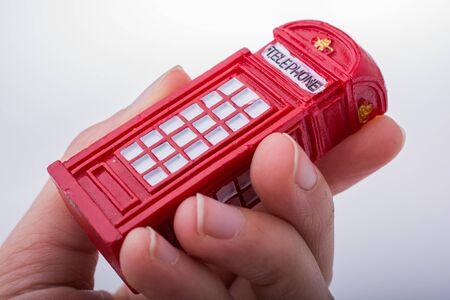 cabina telefonica: Hand holding a red color phone booth on a white background