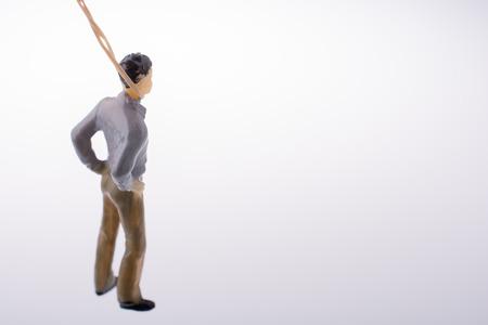 gefesselt: Man figurine gebunden mit einem Seil auf einem braunen backgorund