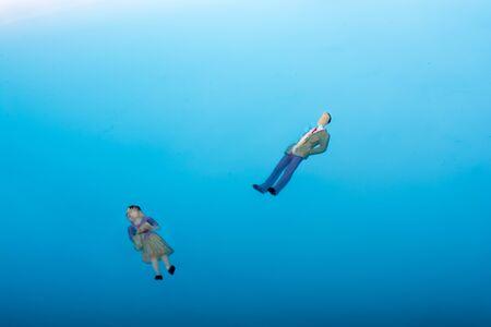 to drown: Pequeñas figuras flotantes en agua azul