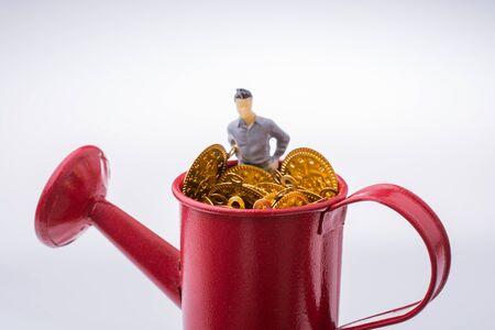 Figurine man standing in a watering can full of fake  gold coins Stock Photo