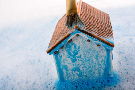domicile: Little model house   and a painting brush in foamy water