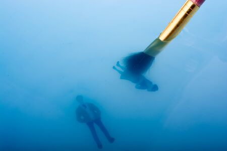 Painting brush and little floating figurines in blue water Stock Photo