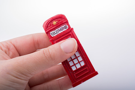 payphone: Hand holding a red color phone booth on a white background