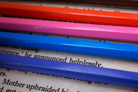 Color pencils placed on the page of a book with text Stock Photo