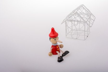 Pinocchio is sitting beside a model house Stock Photo