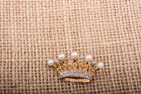 Little model crown placed on a  linen canvas