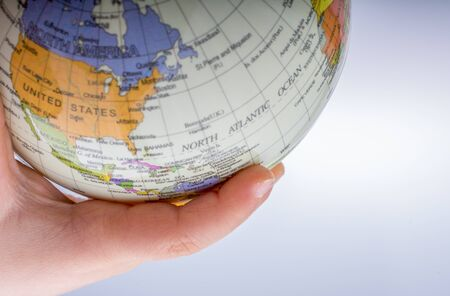 educacion ambiental: Niño sosteniendo un globo sobre un fondo blanco Foto de archivo
