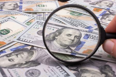 米ドル紙幣の束で虫眼鏡を開催します。 写真素材