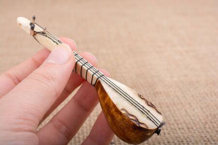 saz: Hand holding turkish musical instrument saz on a linen canvas