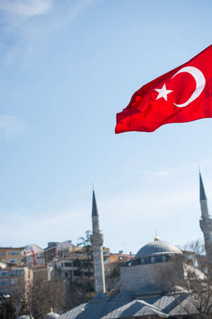 turkiye: Turkish national flag hang on a pole on a rope with a minaret behind Stock Photo