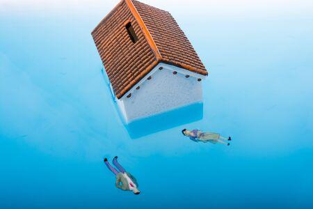 to drown: Pequeña casa de modelo y figurillas de hombre y mujer flotan en el agua