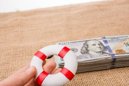 Life preserver in hand over  the banknote bundle of US dollar