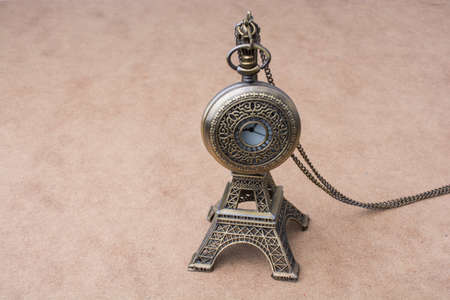 Little model Eiffel Tower  and a pocket watch on brown background