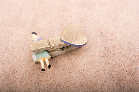 ransom: Woman figurine trapped in a clothespin on ground